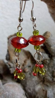 Oorbellen gemaakt van groene en rode glaskralen.