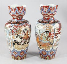 A pair of large Japanese Imari baluster vases, early 20th century, each painted with scenes of battling Samurai warriors and an archer and companion between panels of birds amids trees in a fenced garden, with crenulated neck, 35.25in.