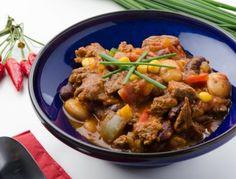 Für das Chili con Carne mit Rindfleisch die Tomaten blanchieren und in kleine Stücke schneiden. Die Zwiebel und den Knoblauch schälen und hacken.