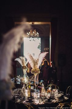 Centrotavola di matrimonio con piume, perle e fiori per tavoli rotondi e bicchiere alto.
