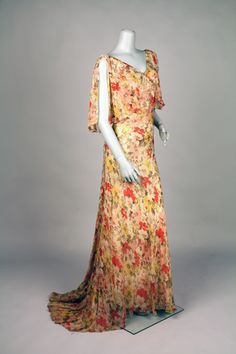 """Dress Accession Number: 2001.104.93 Date Made: 1932-1933 Description: Dress; sheer silk floral print, full length gown. Off-white ground with floral print in red, pink, yellow, olive, brown, and grey. V-shaped neckline in front and a plunging V-shaped neckline in back. Capelet-style """"sleeves"""" sewn to bodice front along neck edge and to diagonal bodice seamline just below bust."""