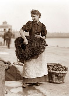 Fisher woman, Whitby, England.  That net would have been very heavy!  Taken by Frank Meadows Sutcliffe, pioneering Victorian photographer.