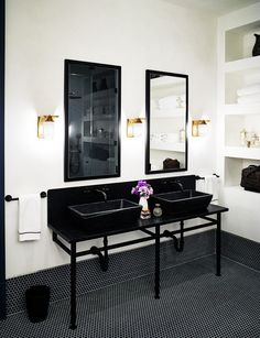 Bathroom with matching black vessel sinks, matching black towel bars, and fancy gold details