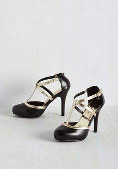 Getting ready to hit the road for a night out? Don't take another step until you buckle into these black stilettos! Starring metallic gold T-straps with a crisscrossing accent, these vegan faux-leather kicks are a pair your shoe collection will miss while you're about town!