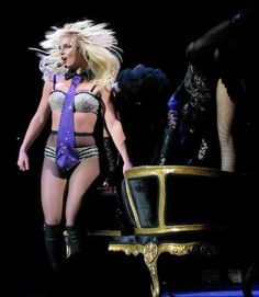 Image of a blond female performer. She has a headset around her hand and is wearing sparkly silver and black lingerie, fishnet stockings and knee-high black boots. She stands in front of a black and golden couch. Britney Spears Tour, Britney Spears Concert, Britney Spears Albums, Hedwig Costume, Baby One More Time, Rite Of Passage, Sean Connery, Fishnet Stockings, Stage Outfits