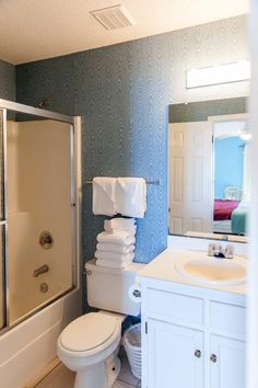 Old tiles, outdated wallpaper and a shower and tub combo weren't doing this guest bathroom any favors.
