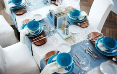 A view from above of a dining table set formally with a white and blue color scheme.