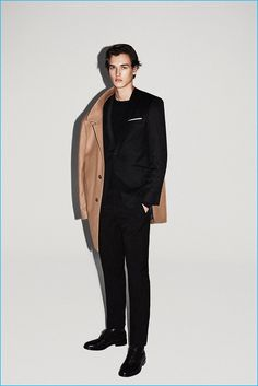 Tap into refined, elegant style with a camel overcoat and a black wool suit. Why not add black leather derby shoes to the mix for a more relaxed feel?   Shop this look on Lookastic: https://lookastic.com/men/looks/overcoat-suit-long-sleeve-t-shirt/23203   — Black Long Sleeve T-Shirt  — White Pocket Square  — Black Wool Suit  — Camel Overcoat  — Black Leather Derby Shoes