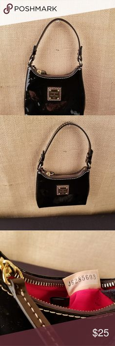 Dooney and Bourke Bitsy bag wristlet Authentic Dooney and Bourke Bitsy bag. Patent leather in Black.  Includes  Inside zippered pocket and key clip. ITEM# PT 250 BL Outside in excellent condition no rips or tears. Shiny black patent leather. Inside has many tiny little income marks see photo for details! It is a tiny wristlet. Dooney & Bourke Bags Clutches & Wristlets