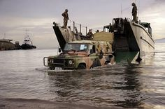 An Australian Army Land Rover disembarks a landing craft onto a beach in Ormoc, Philippines, during Operation PHILIPPINES ASSIST.