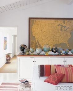 a collection of antique and vintage globes is a whimsical companion to a large vintage map of America