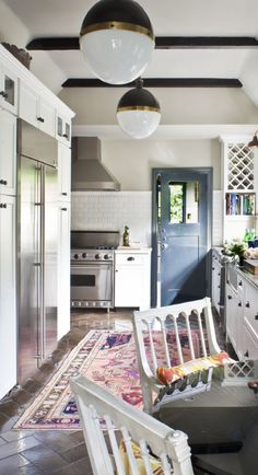 love the white cabinets & tile/dark floors/rich colorful rug combo.