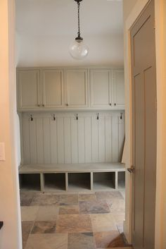 mudroom with soft green woodwork and slate floors. jvw home