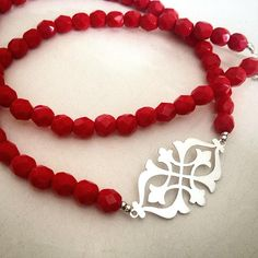 Hand cut sterling silver arabesque on luscious red faceted bead necklace.