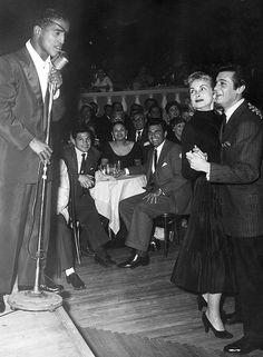 Sammy Davis, Jr. sings as Tony Curtis and Janet Leigh  watch him from the dance floor, Ciro's nightclub, 1955.