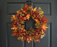 An autumn wreath with realistic artificial fall berry, acorns, pinecones, and fall leaves. A grapevine pumpkin is nestled into the wreath. The