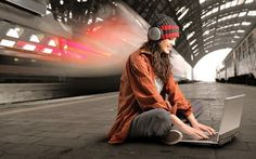 Girl with headphones and laptop in the station wallpaper
