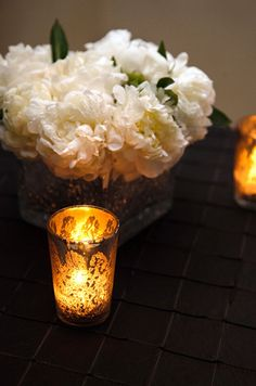 Tea candles in golden containers light an arrangement of white peonies.
