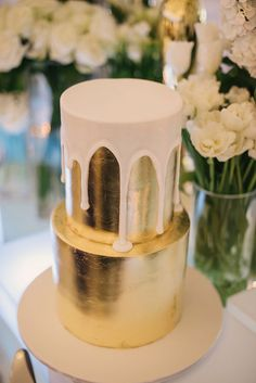 gold metallic wedding cake with dripping white icing