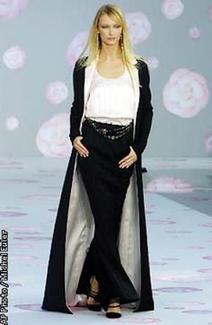 A model sports a long black coat over matching trousers and a white decollete top designed by German fashion designer Karl Lagerfeld for Chanel's spring-summer 2002 Haute Couture collection, presented Tuesday Jan.22, 2002 in Paris