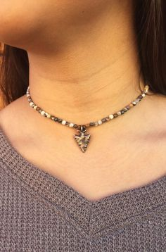 Add a little edge to your outfit with the our new Tucson Choker. It has rhyolite beads whose neutral colors pair perfectly with anything in your closet. By adding the brass arrowhead this choker is tr