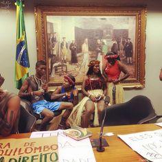 Figura e fundo. Indígenas durante vigília em plenário de comissões da Câmara à frente de um quadro sobre Tiradentes e da bandeira nacional