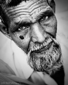 Black and white portrait of an old man with beard looking up from Mumbai  by Joshi Daniel