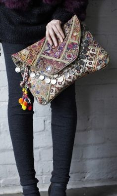 Oversized envelope clutch bag made of vintage fabric panels. Richly decorated with coins, mirrors and pom pom tassels.