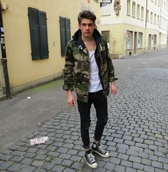 black converse , black jeans , t shirt tee , and a camo coat jacket , summer - the jacket