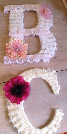 Large wooden letters wrapped with lace ribbon and adorned with no-sew fabric flowers.  Made these for my little neices.  Perfect for a shabby-chic nursery or dainty little girl's bedroom wall!