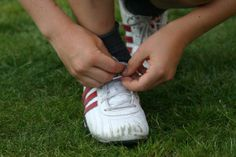 Boy lacing up his sneakers in the grass.