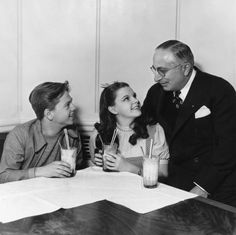 In costume as Dorothy, Judy Garland takes a sweet break with frequent musical sostar Mickey Rooney and gets a visit from MGM head Louis B. Mayer, who signed her to the studio in 1935.