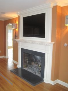 Recessed TV behind a custom built frame over the fireplace.