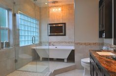 A lovely master bathroom featuring large format travertine tiles throughout the space. A thin strip of mosaic tile along the bottom third of the walls breaks up the tile and adds color. A simple circular crystal chandelier hangs above the trapezoidal soaking tub. An enclosed fireplace sits above the tub as well, adding further ambiance.