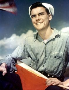 Low-angle portrait of American Seaman First Class Paul J. Melody as he holds signal flags during a trip along the Seine River to deliver supplies to Paris, France, 1944. (Photo by PhotoQuest/Getty Images)