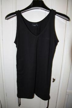 Casallin musta toppi, tukevaa kangasta, sivuissa molemmilla kyljillä narut, joista voi kiristää ryppyyn ja paidan lyhyemmäksi.