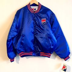 """NWT vtg NBA Sac Kings satin bomber coat jacket XL Vintage NBA Sacramento Kings NWT satin bomber coat adult unisex size XL. Royal blue & Red accents. Brand new with Original Tags varsity satin jacket by Swingster. Originally from 80's and 90's Like OG Starter coats from 80s and 90s urban street wear. Lightweight interior lining size XL also fits size Large. Mint Deadstock Pristine VTG nylon jackets w 2 pockets & embroidered logo on chest. Striped ribbed collar & cuffs. ApproxPit to Pit 28""""…"""