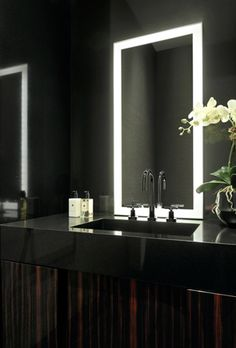 In the guest powder room, a sink carved out of a single block of black granite sits atop a custom vanity in high gloss macassar ebony. The special mirror is designed with integrated lighting. Walls are lined with a silver silk.