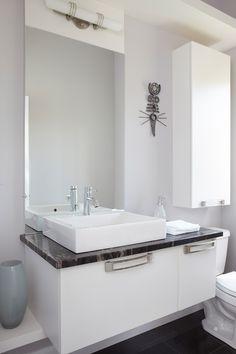 Le blanc immaculé de ces meubles de salle d'eau en MDF laqué est mis en valeur par des poignées décoratives et un comptoir de granit Titanium Black contrastant.