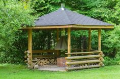 This is a unique rustic gazebo with a brick grill at the center. Perfect for a bit of outdoor camping-style cooking!