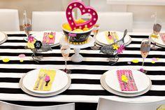 mesa posta com toalha listrada p&b pratos brancos e guardanapos estampados de passarinho.