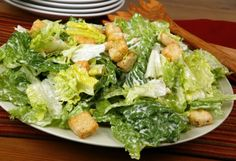 Caesar salad with: light and dark lettuce, croutons, dressing, and cheese.