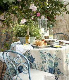 "Camellias arch over an outdoor dining table draped with a Clarence House linen, Dahlia. ""Crisp hemstitch linen napkins, candlelight, jasmine in a 19th-century bowl--these are simple and refined luxuries,"" Reid says. Chairs are vintage French."