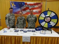 """Sgt. John Watson with soldiers Allen and Preller, along with Shattuck-St. Mary's 11th grader Kourtney Menches, at the Faribault Business Expo on April 25th, 2013. Attendees were given the opportunity to """"Spin the Wheel"""" and win prizes, including military MRE's (Meals Ready to Eat). Buy this Prize Wheel at http://PrizeWheel.com/products/tabletop-prize-wheels/tabletop-black-clicker-prize-wheel-12-slot/."""