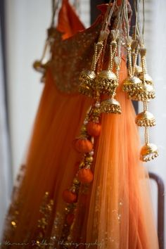 Bridal Details - Orange Sequinned Net Lehenga with Gold Latkans and Orange Pom Poms | WedMeGood #wedmegood #orange #pompoms #latkans #bridal