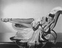 Burlesque dancer Mary Mack reclining on a chaise longue, circa 1950.