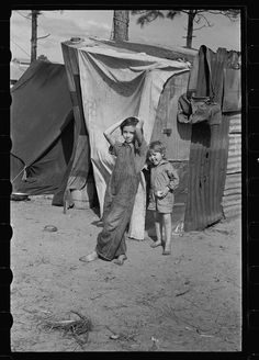 1933 Winter Haven, Florida. From Department of Agriculture report on living conditions of migrant workers. A family of 8 lived in this tent shanty outside a citrus processing plant.