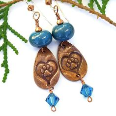 If you love dogs or know someone who does, the HEART OF A DOG handmade earrings are a perfect jewelry gift. The one of a kind earrings were created with artisan copper teardrops stamped with a paw print encircles with a heart, dark turquoise lampwork glass beads and Swarovski crystal dangles.