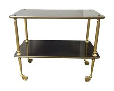 Vintage French serving cart on wheels.  Dark faux wood high gloss laminate over wood.  Accented with decorative  brass banding around both levels as well as fluted brass legs and interesting brass accents covering the wheels.  Lots of detail in the brass work in every area.  The laminate is easy to clean and very durable with two levels for lots of options. From the Brittany region of France.