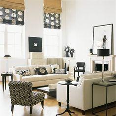 living rooms - black roman shades white sofas black pillows black slipper chair glass lamp fireplace black pedestal table iron black console table